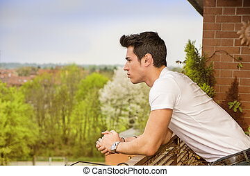 Handsome dark haired young man looking out on balcony -...