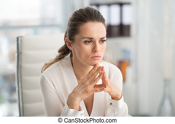 Pensive businesswoman with hands in steeple position - At...