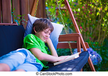 Child reading a book in the garden - Happy school boy...