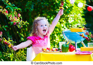 Little girl at garden grill party - Children grilling meat....