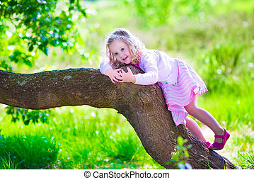Little girl climbing a tree - Little girl hiking in a...