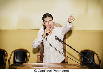 Passionate Man Speaking into Microphone in Meeting -...