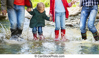 Happy family wearing rain boots jumping into a mountain...