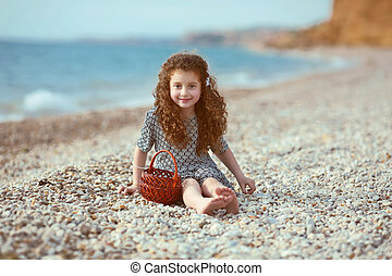 Funny little girl with long curly hair resting on the beach....