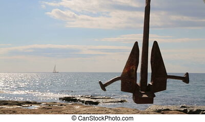 Black Anchor Swinging At Seaside