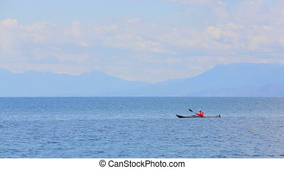 Man Rowing In Canoe In The Sea - This is a picturesque side...