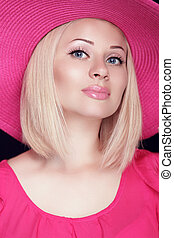 Beautiful blond woman with makeup, smiling girl posing in pink hat.