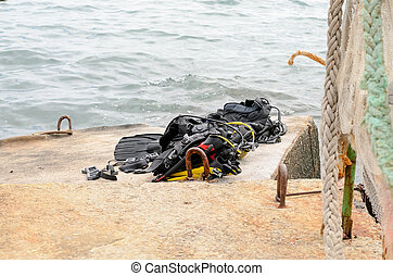 Pile of Scuba Diving Equipment Drying on Dock - Pile of...
