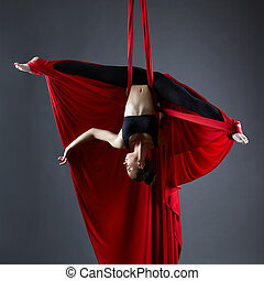 Graceful dancer on aerial silks posing upside down - Image...
