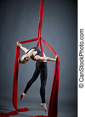 Attractive dancer posing with aerial silks at camera