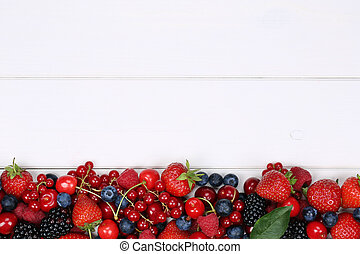 Berry fruits on wooden board with strawberries, blueberries, cherries and copyspace