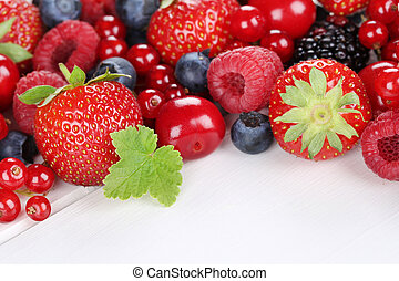 Berry fruits on wooden board with strawberries, blueberries, cherries