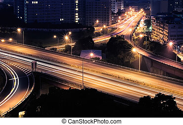 Highway interchange in night with cars light and dark...