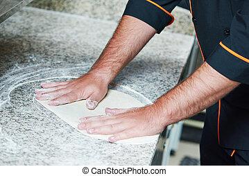 Pizza preparartion - hand of chef baker in uniform preparing...