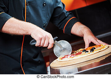 Pizza preparartion - cutting - Closeup hand of chef baker in...