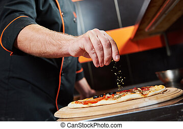 Pizza preparartion - hand of chef baker in uniform adding...