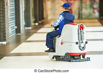 worker cleaning store floor with machine - Floor care and...