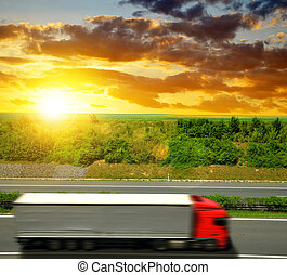 Truck on the highway at sunset.