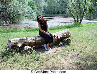 Young woman sitting near the lake