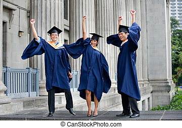 Graduates Fist Pump - Three young graduates pump their fists...
