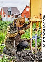 Welding pipe - Welder with mask soldering pipe outdoor in...