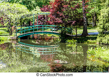 Green Bridge Over Calm Lake - A beauifully landscaped...