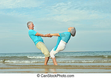 Elderly couple walking along seashore - Beautiful happy...