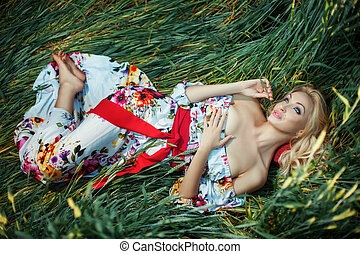 Beautiful blonde lying on the grass crumpled She has dreamy...