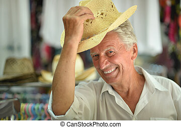 Senior man at shop hats - Portrait of senior man at shop...