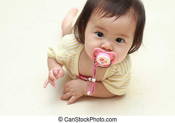 baby girl sucking on a pacifier