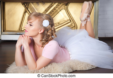 Ballerina with flower in her hair lying on the floor -...