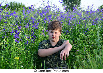 teen boy with allergies in flowering herbs - A teen boy with...