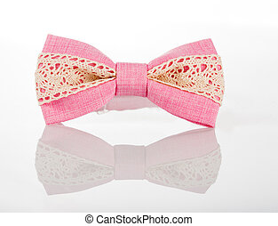 pink bow tie with white lace on a white background with...