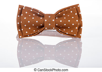 Brown bow tie on a white background with reflection