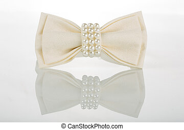 white bow tie with pearls on a white background with...