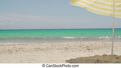 Beach umbrella on a sunny tropical beach with golden sand...