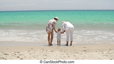 Little girl playing at the seaside with her family