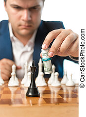 Conceptual shot of money power. Man making chess move with...
