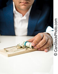 Closeup of businessman taking money lure from the mousetrap...