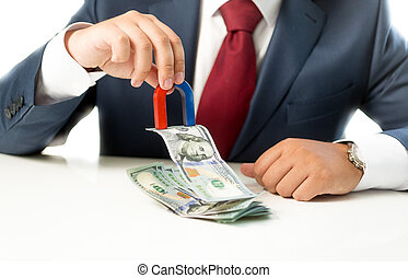 businessman pulling money from stack on table with the...