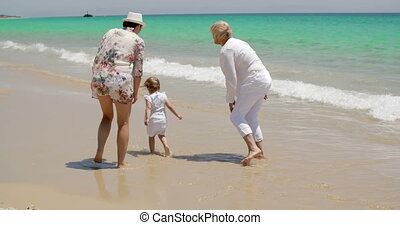 Girl Enjoying at the Beach with Mom and Grandma - Little...
