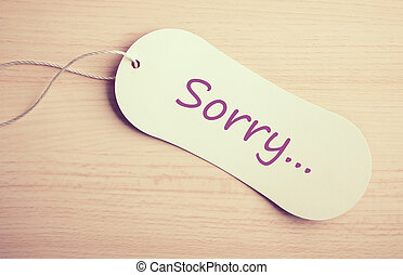 Sorry label is on the wooden desk background.