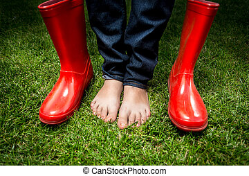female feet standing on green grass next to red rain boots -...