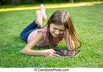 girl lying on grass and using tablet