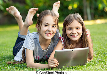 two cute smiling girls lying on grass at park with digital...