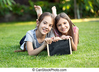 Portrait of two smiling girls lying on grass with chalkboard...