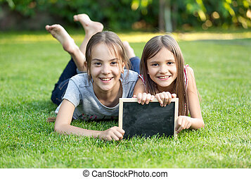 Portrait of two girls lying on grass with chalkboard