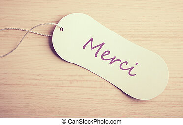 Merci label is on the wooden desk background.
