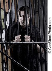 Adolescent - Young man in an alley behind steel bars