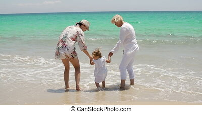 Grandma and Mom Holding Little Girl at the Beach - Rear View...